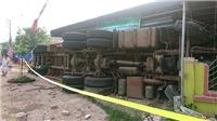 Ba căn nhà bị xe container lật nghiêng, đè sập