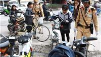 Từ ngày 1/7 xử phạt người đi xe máy, xe đạp máy không đội mũ bảo hiểm đúng quy cách