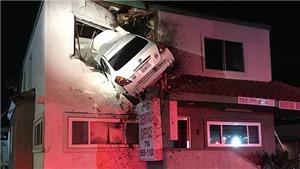 Xe ô tô bay lên rồi treo lơ lửng trên tầng 2 tòa nhà ven đường